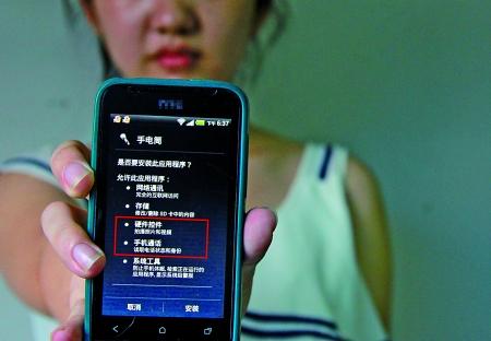 """网友""""奶粉姐姐""""安装的手电筒软件,却要求开放手机通讯录等不相干权限。 记者 郑旭鹏 摄"""